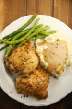 A white plate holds two golden, crispy baked chicken thighs, some green beans, and a pile of mashed potatoes with gravy.