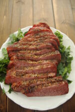 A slab of oven roasted corned beef is sliced thickly on a white plate. There is green, leafy herbs for garnish on the sides.