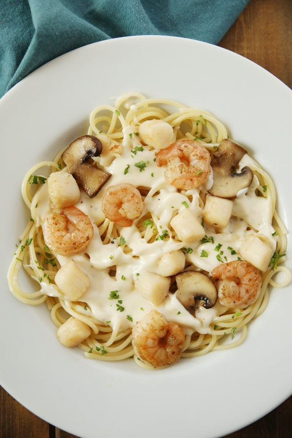 A white plate is full of tender shrimp, sweet bay scallops, and plenty of alfredo sauce drizzled over pasta.