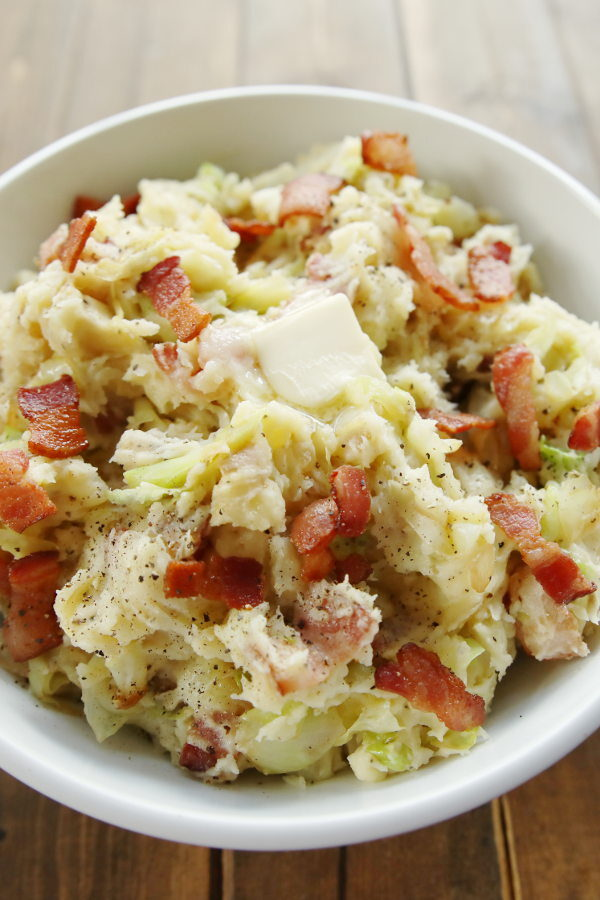 A large white bowl full of Irish colcannon. You can see large pieces of bacon and chunks of tender cabbage and a pat of butter melting on top.
