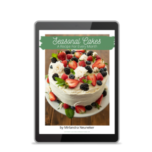 A cover image of the Seasonal Cakes Cookbook features a lovely fruit and flower covered layer cake with buttercream frosting.