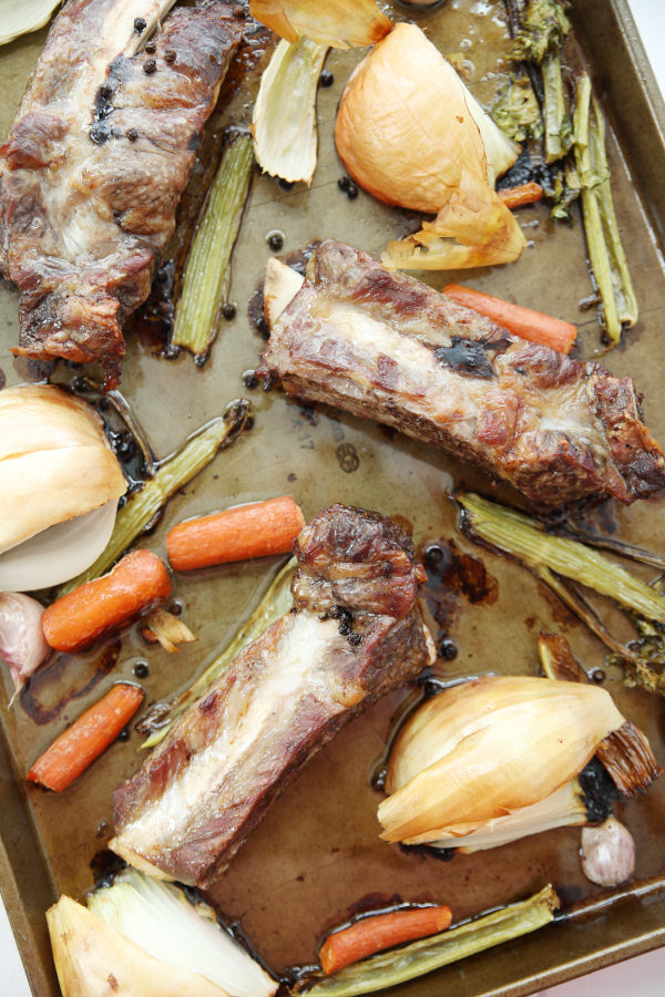 Roasted beef rib bones and vegetables are beautiful golden brown after roasting on a baking sheet.