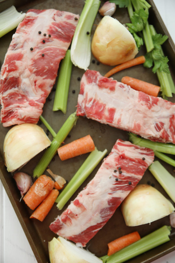 Beef rib bones, celery, onions and carrots are arranged on a baking tray before roasting for stock.