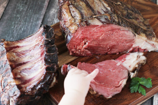 A little boy pulls a slice of prime rib off of the carving board.